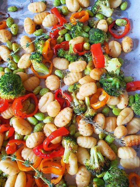 A baking sheet full of baked veggies , gnocchi and herbs.