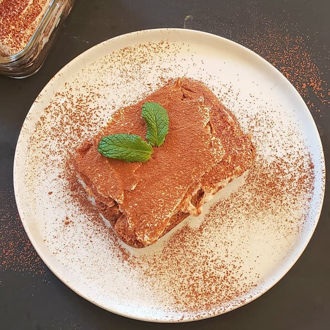 A white dessert plate with a slice of layered tiramisu dessert served with mint leaves and cocoa powder dusting on the top.