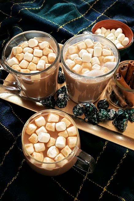 overhead shot of 3 glass filled with warm cocoa drink . The cups are on silver tray along with chocolates, cinnamon sticks and marshmallows.