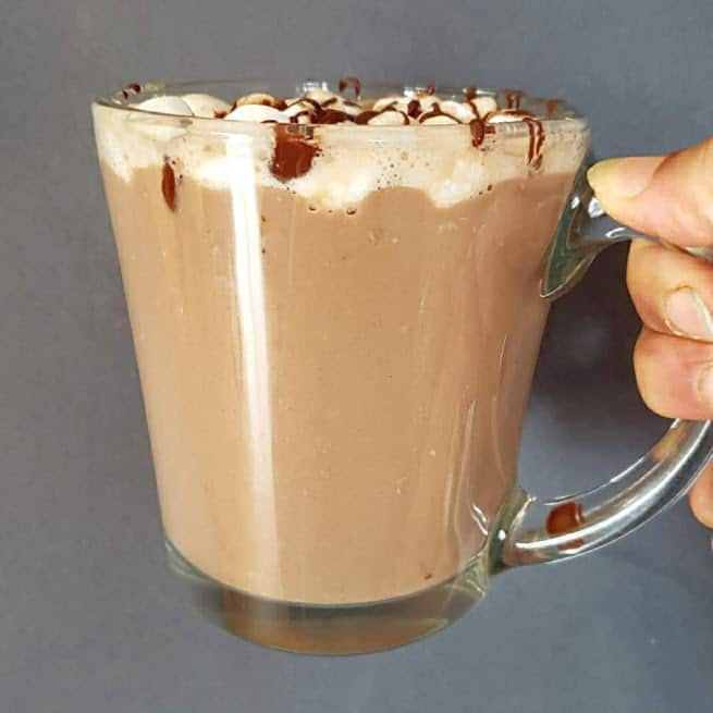 A hand holding a mug filled Homemade Hot Chocolate. It shows creamy and rich colors of the drink.