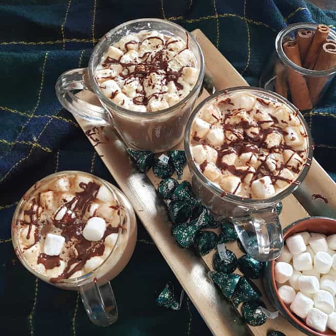 Homemade hot chocolate drink served in three glass mugs along with chocolate bites and marshmallows served on silver tray. The whole set up is served on cozy blanket.