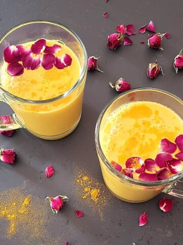 Two glasses filled with homemade turmeric latte served with rose petal garnishes.