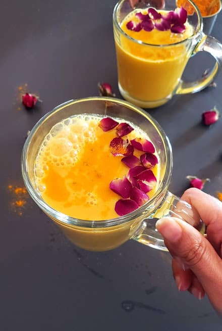 A hand holding a glass of yellow milk garnished with rose petals and turmeric.