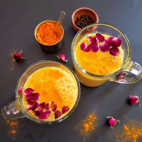 Golden yellow Turmeric Milk served in two glasses.