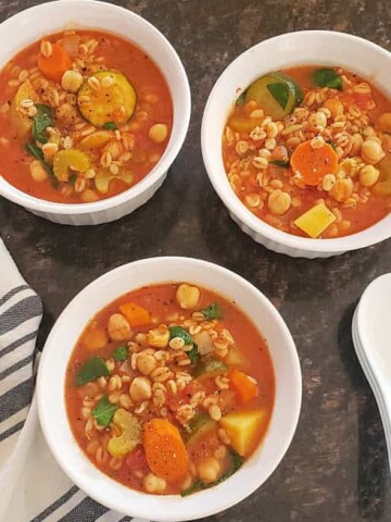 A dinner serving of three soup bowls full of vegetable barley soup. The soup spoons and kitchen towel is on the side.