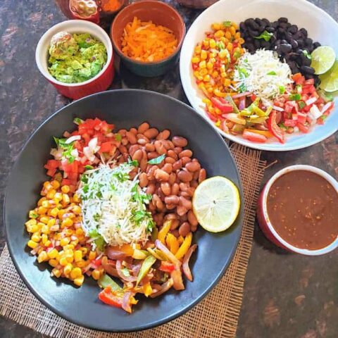 A dinner serving of two plates with colorful tex mex ingredients. These tortilla less Vegetarian Burrito Bowls are filling and flavorful.
