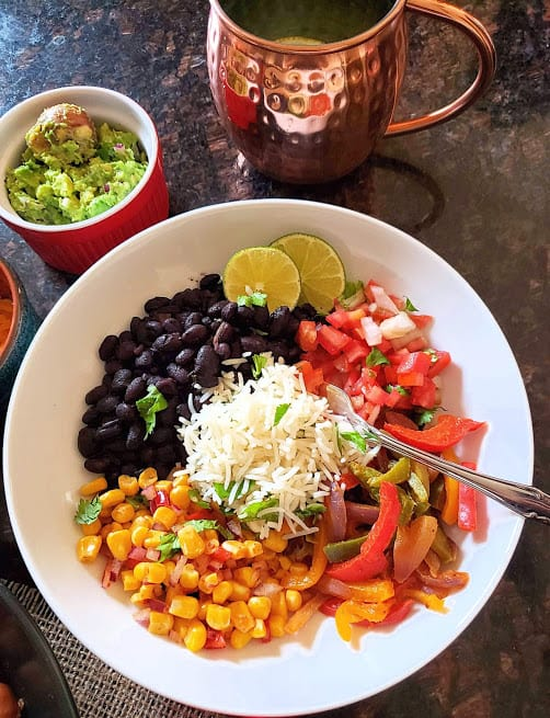 A white dinner serving bowl filled with black beans, fajita veggies, corn, rice and other trimmings.
