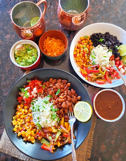 An overhead image of two bowls filled with burrito fillings and various toppings along with 2 copper mug drinks.