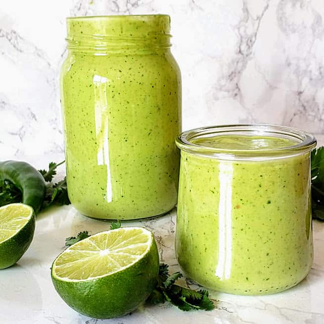 Creamy and delightful Avocado Cilantro Lime dressing poured in the glass bottle and a serving cup.