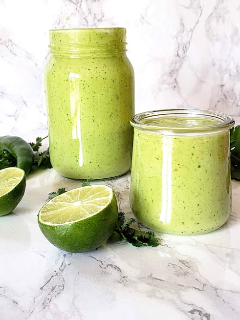 A glass bottle and a cup full of green salad dressing made with avocado, cilantro and lime along with other ingredients.