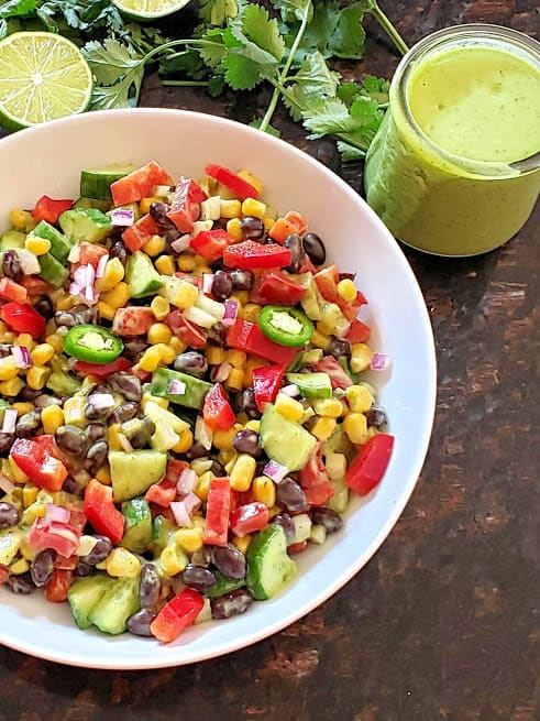 A bowl of black bean and corn salad along with cilantro lime dressing.