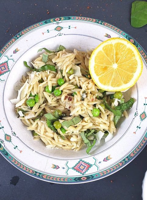 A bowl with creamy pasta garnished with lemon wedges.