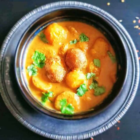 Dum Aloo served in a dinner bowl. This creamy Indian dinner Curry is made with baby potatoes and cooked in the instant pot or stove top.