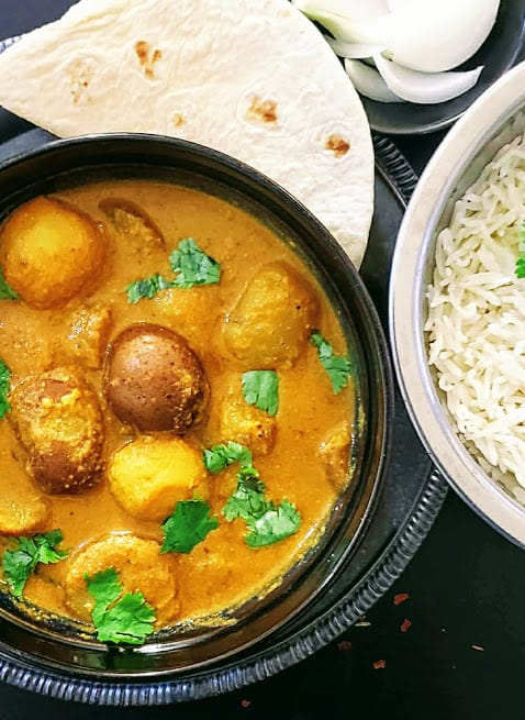 Creamy potato gravy curry served with rice, roti and onions