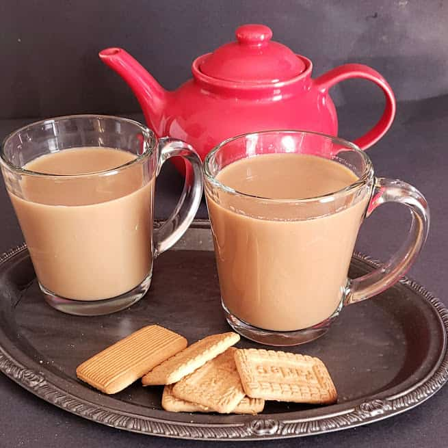 A red tea kettle and two glass cups filled with Indian Spiced tea latte. This masala chai is served with tea cookies.