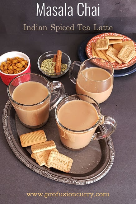 Indian spiced milk tea served in three glasses along with cookies and snack.