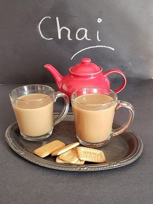 A red kettle and two glasses filled with Chai tea.
