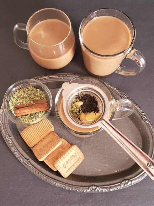 A tea cup and a strainer on the serving tray along with cookies and spices used in making milk tea latte.