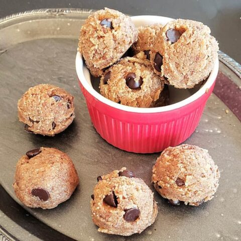 A red bowl filled with almond flour chocolate chip edible cookie dough balls along with a serving tray.