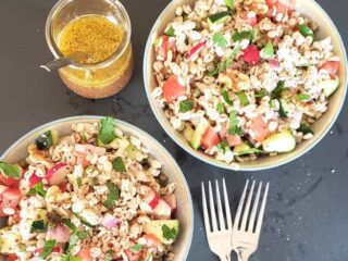 Two salad bowls filled with grain based barley salad with vegetables. Maple Dijon Mustard salad dressing is on the side.