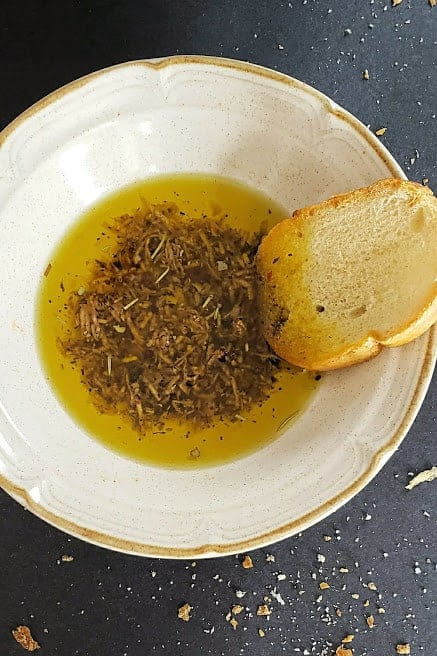 A bowl filled with Italian herb bread dipping oil.