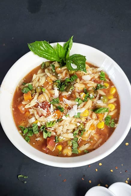 A soup bowl filled with vegan orzo soup and garnished with cheese, herbs and black pepper.