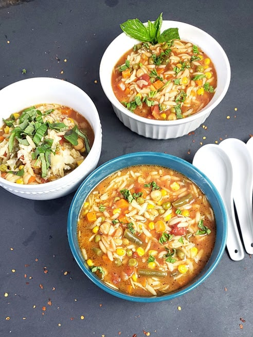 A dinner serving with three soup bowls filled with hearty one pot chickpea orzo soup.