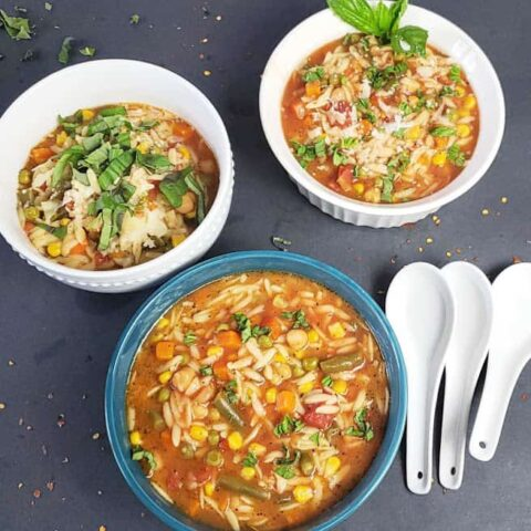 Delicious and easy Vegan Chickpea Orzo Soup garnished and served in soup bowls.