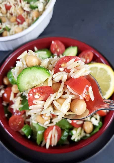A spoonful of salad showing al dente orzo pasta, cherry tomato and persian cucumber.