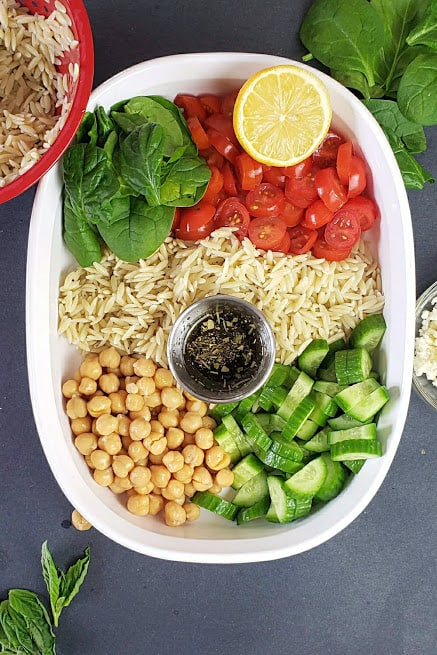 Process step showing all ingredients arranged in a salad bowl just before adding the dressing.