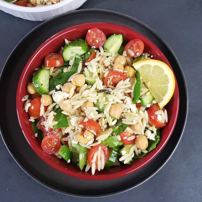 Quick Orzo Pasta Salad with chickpeas and veggies served with freshly made dressing served in a salad bowl.