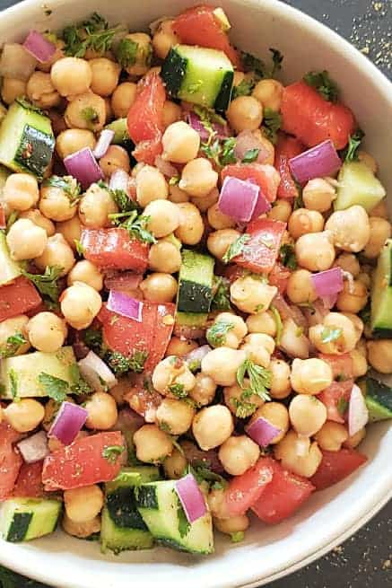 A close up image showing colorful veggies and cooked chickpeas tossed together in zesty lemon dressing.