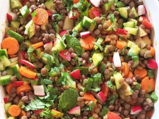 close up image showing tender lentils, colorful veggies and chopped herbs tossed in curry lemon dressing.