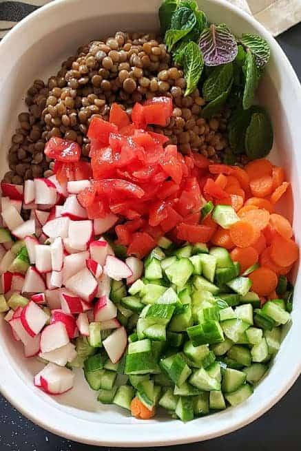 Process step showing all the ingredients gathered together for making a vegan lentil salad.