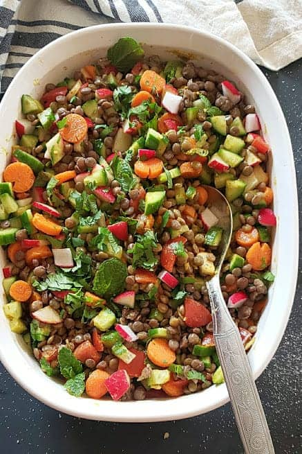 An overhead image showing a salad bowl full of lentil vegetable salad along with serving spoon.