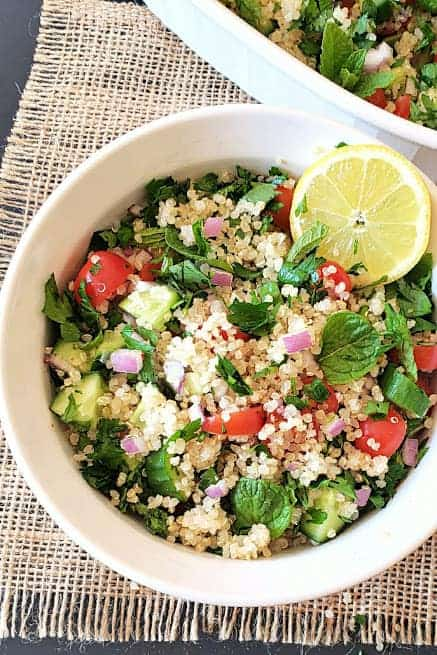 A white salad bowl full of freshly made herb quinoa salad.