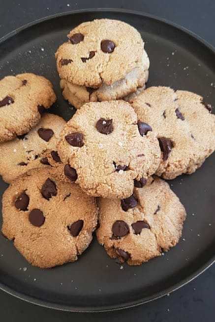 Sea salt dusted chocolate chip cookies served on black serving plate.