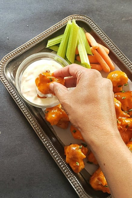 A hand holding a spicy cauliflower nugget and dipping it into sauce.