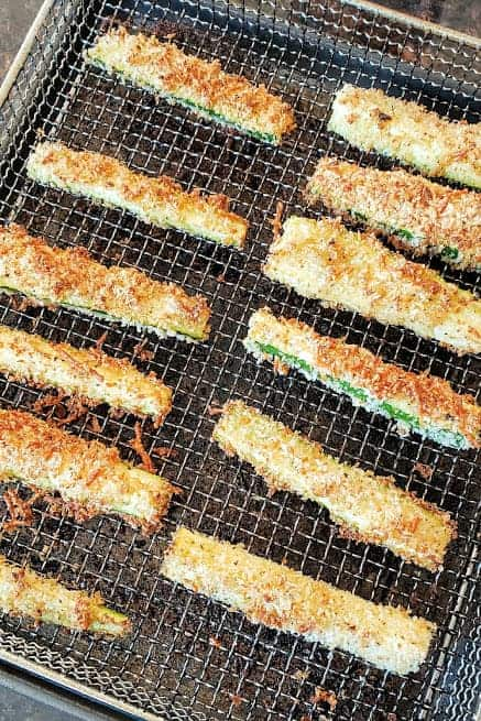 Zucchini fries arranged in a single layer on the air fryer basket.