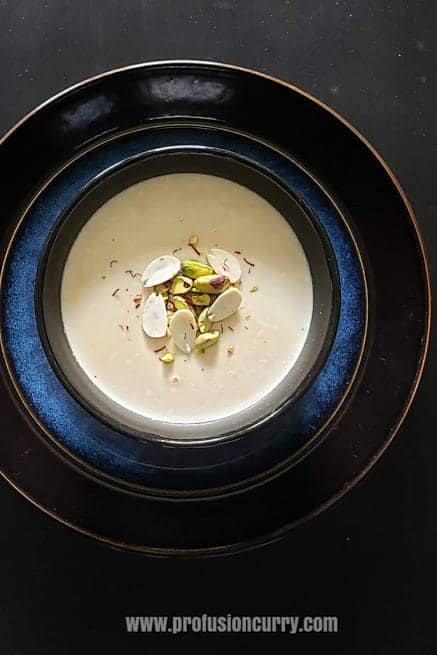 Mishti Doi served with saffron and chopped almonds and served in black dessert bowl.