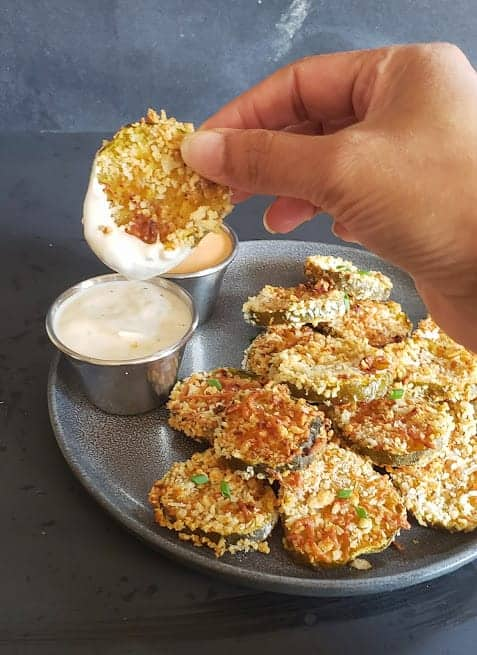 A hand holding fried pickle slice and dipping it in the sauce.