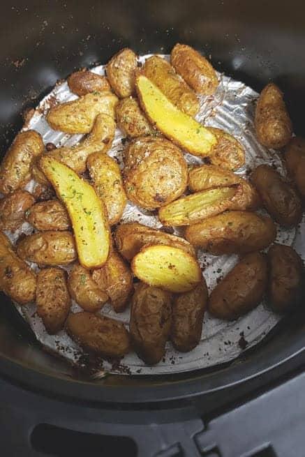 Freshly roasted baby potatoes in the air fryer basket.