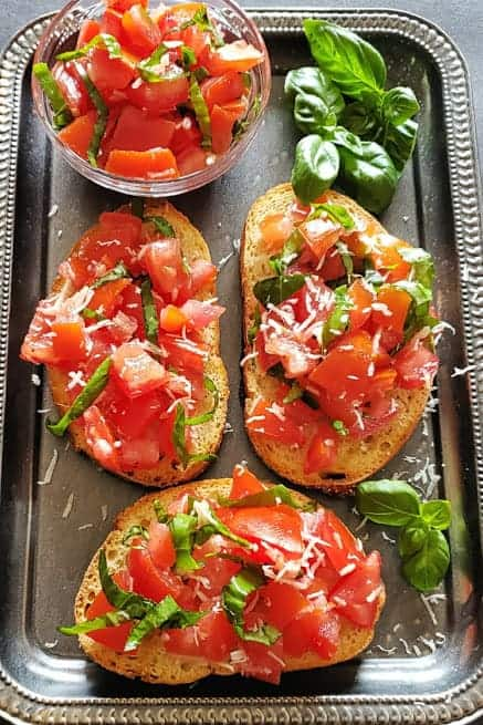 An overhead shot of platter filled with 3 bread slices topped with tomato bruschetta and fresh basil leaves.