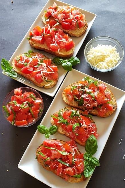 A party platter full of homemade bruschetta served on white appetizer plates.