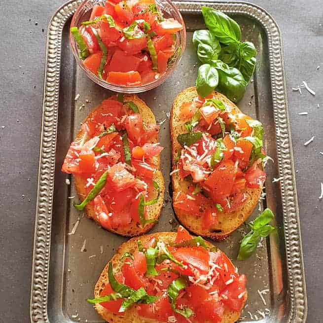 Tomato basil bruschetta served on bread toasts along with fresh basil and tomato mixture.