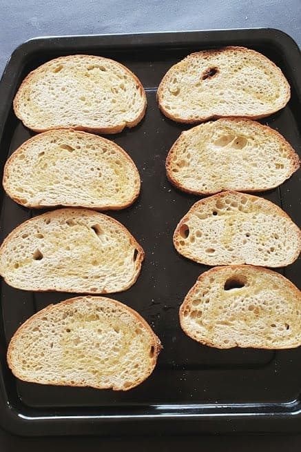 Eight bread slices arranged on baking sheet to be toasted.
