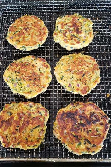 Freshly homemade zucchini fritters on the air fryer basket.