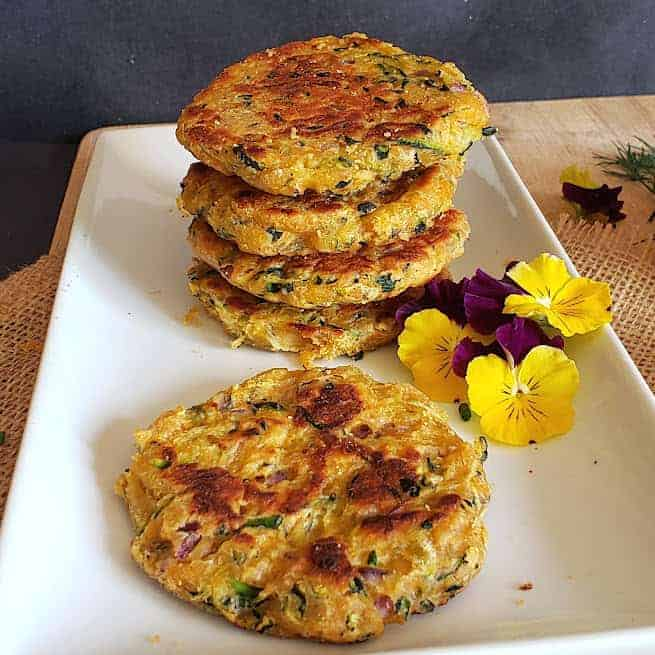 Vegan and gluten free zucchini fritters made in air fryer and served on a platter with garnishes.