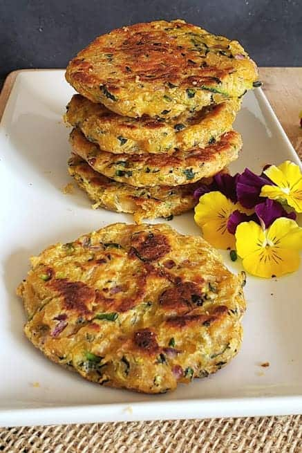 Five gluten free zucchini fritters stacked and served on a serving platter.