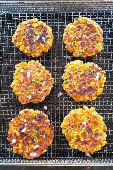 Corn fritters freshly made in the air fryer basket.